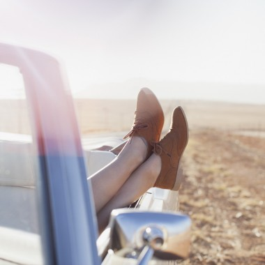 woman on road trip feet up convertible