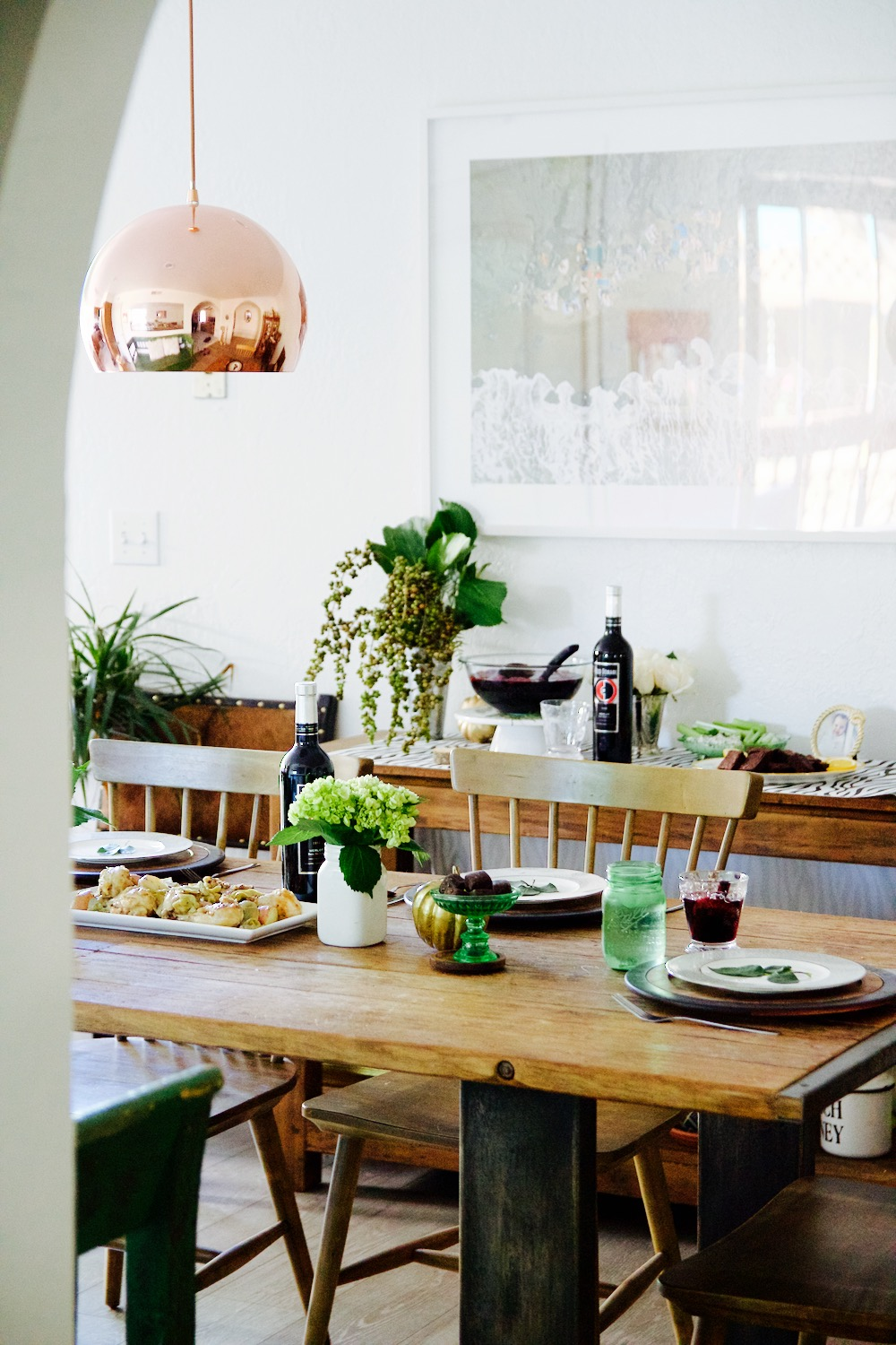Green and gold holiday entertaining setup with rose gold lamp