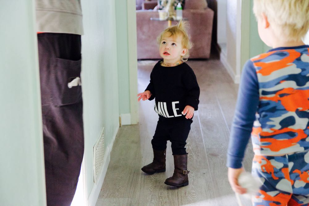 Baby in black and white Smile sweatshirt and brown boots