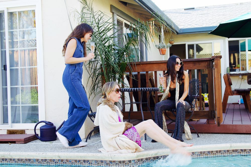 Three women wearing vintage inspired outfits by a pool