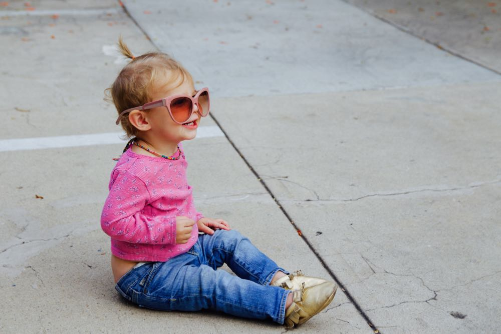 baby wearing sunglasses and gold freshly picked shoes