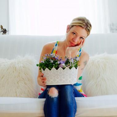 Jordan Reid on white couch holding basket of flowers