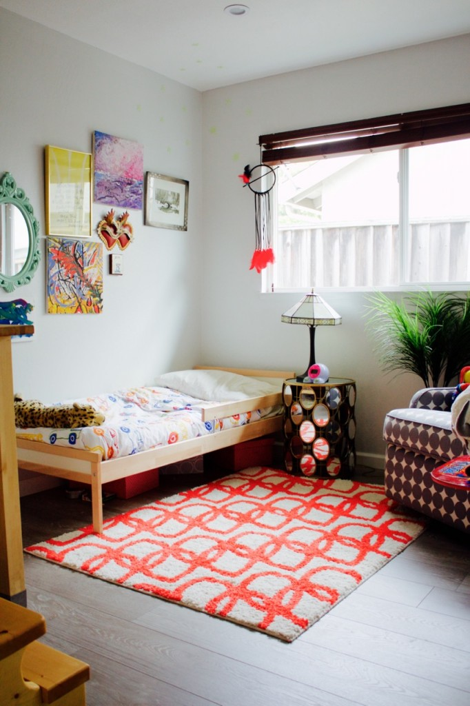 Bright little boy's bedroom with red and white rug and eclectic gallery wall