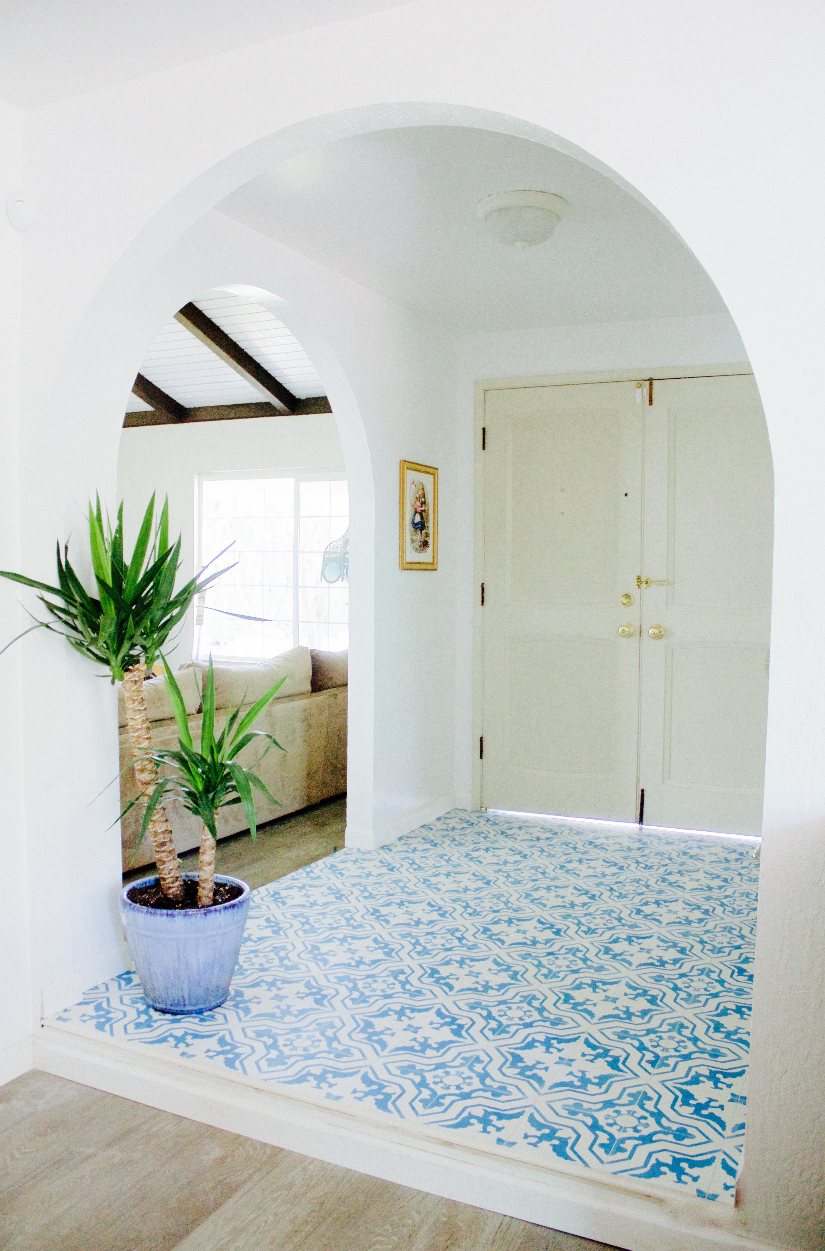Bold blue and white entryway tile with white walls