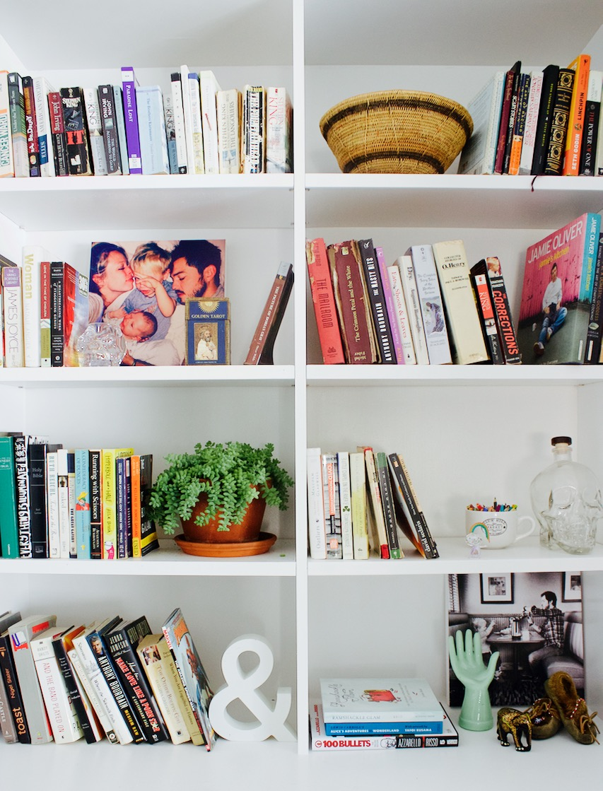 A bookshelf display with photos, books and a crystal skull