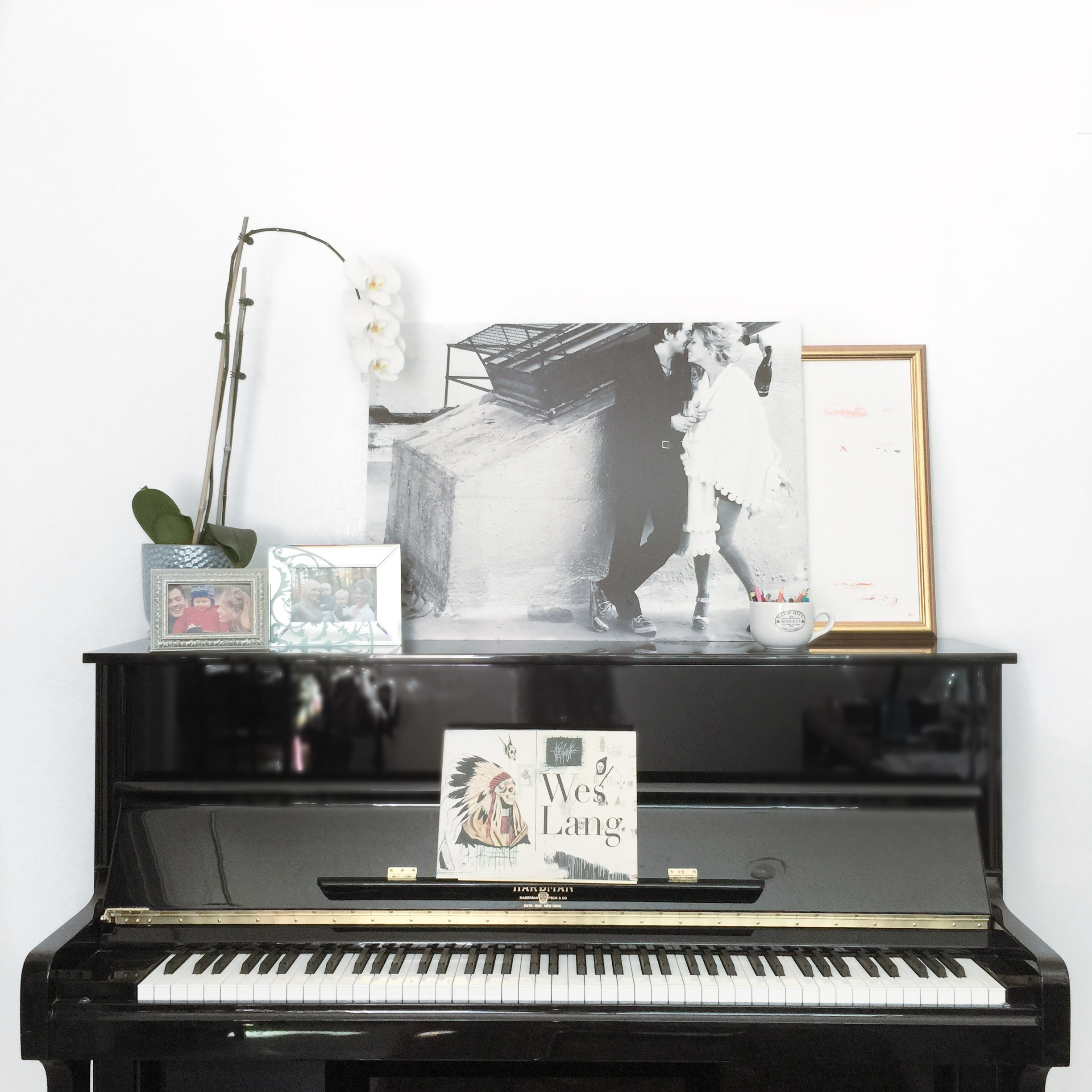 Black piano with orchid, photos and paintings on top