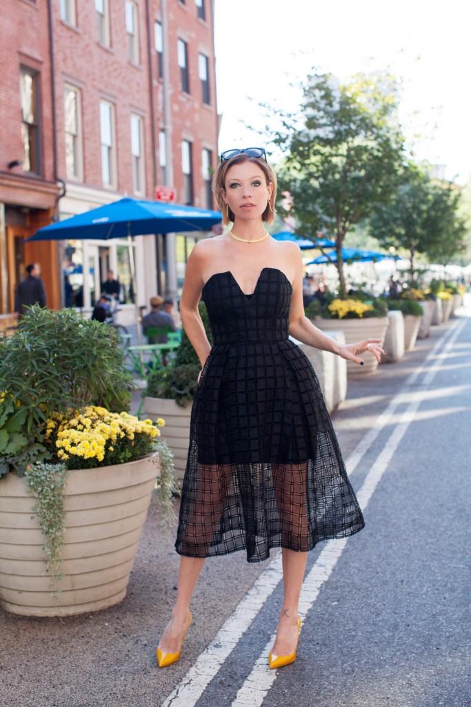 Jordan Reid wearing a little black dress from Saks Fifth Avenue and yellow Christian Louboutin heels