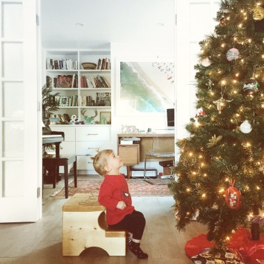 baby girl in red sweater looking at christmas tree