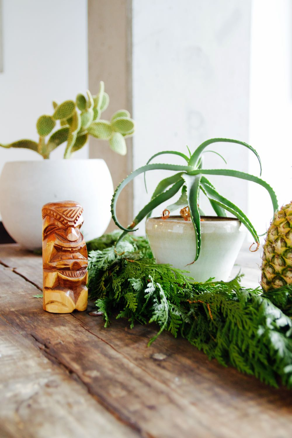 succulents, a tiki cup and a garland for a retro holiday tablescape