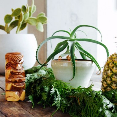 tiki inspired holiday tablescape with green and white elements