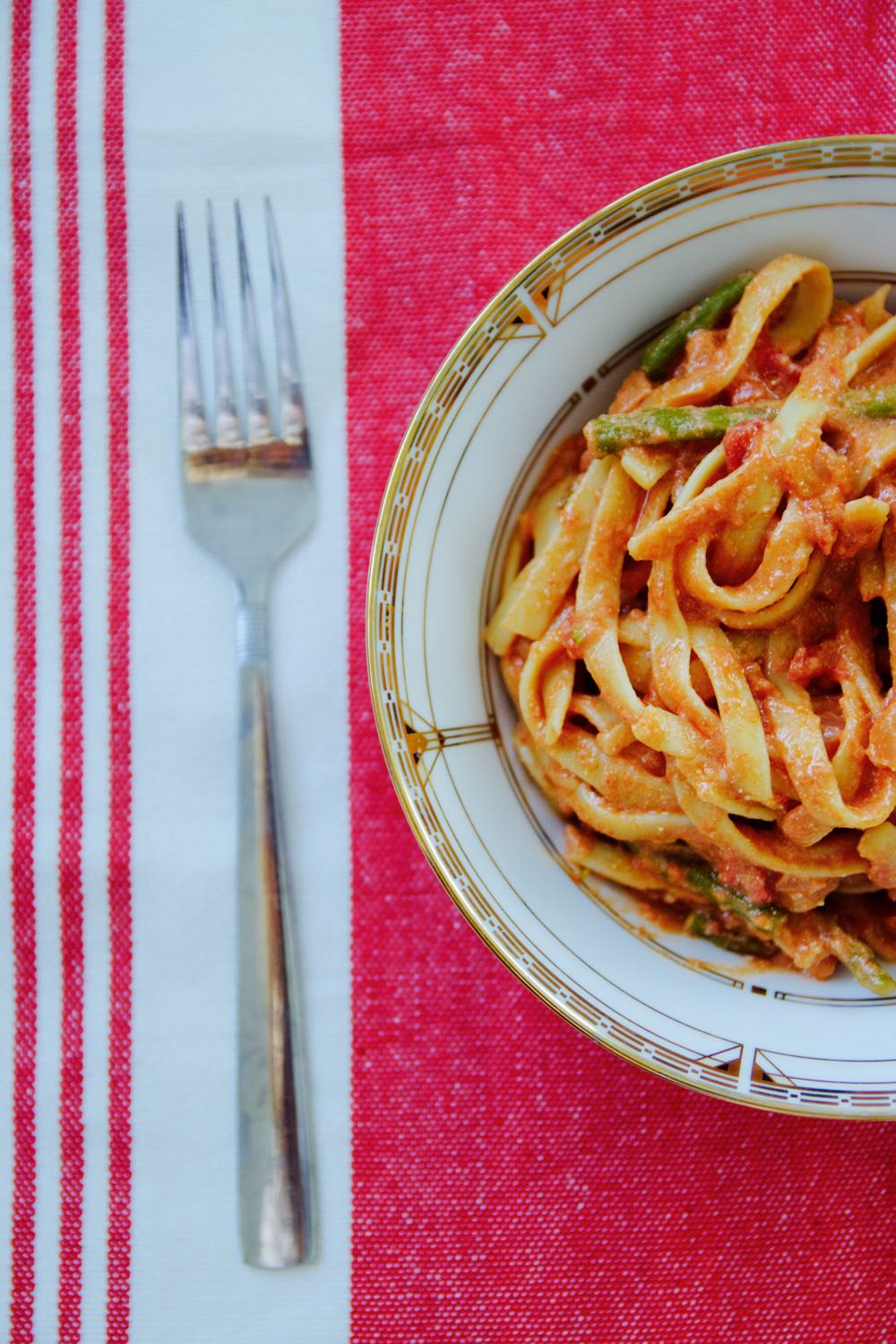 fettuccine with sweet tomato sauce, ricotta and asparagus on a red and white tablecloth