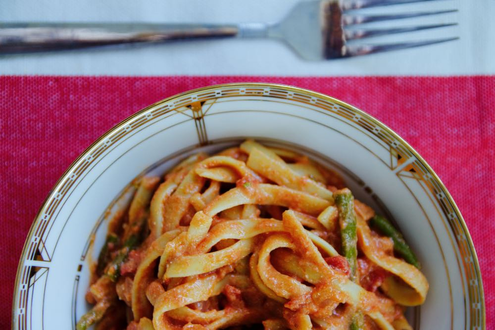 fettuccine with sweet tomato sauce and asparagus on a red and white tablecloth