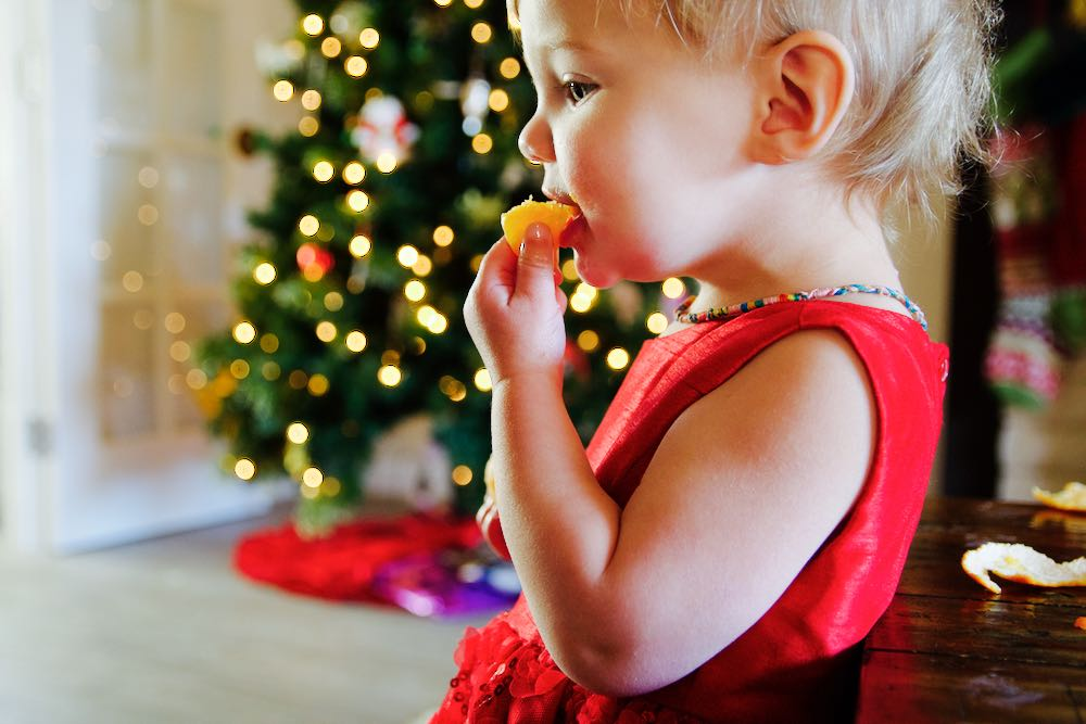 little girl eating orange in front of the christmas tree
