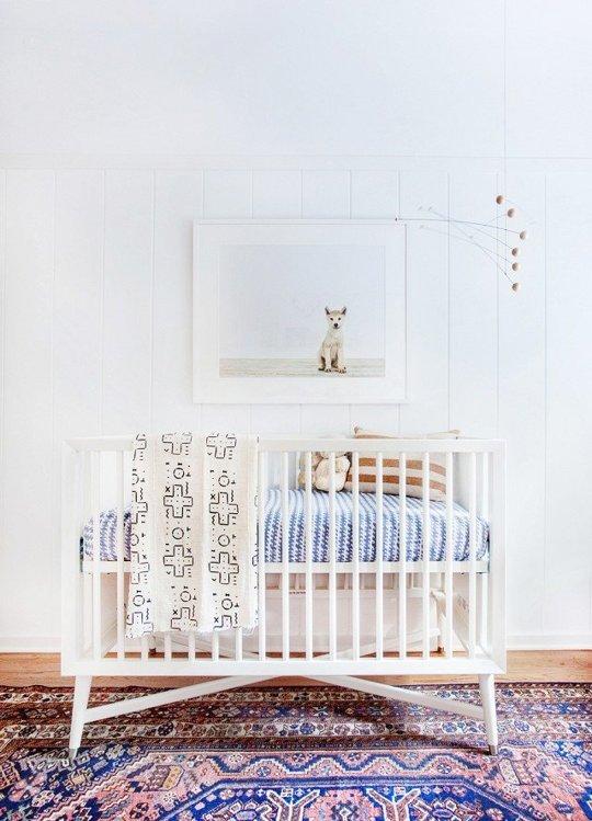 white nursery with a white wrought-iron crib