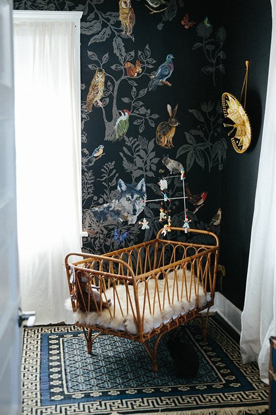 super cool nursery with a black wall and a wicker crib