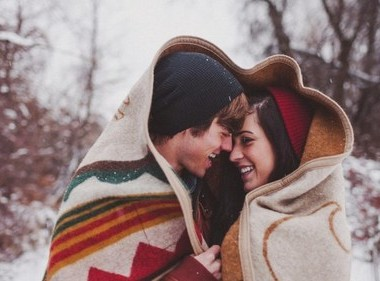 Christmas couple wrapped in vintage wool blanket