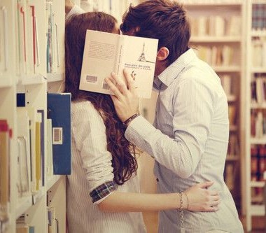 Couple kissing in a library behind a book