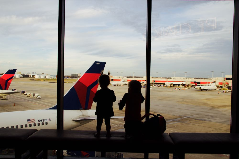 Children watching a plane take off from inside the terminal