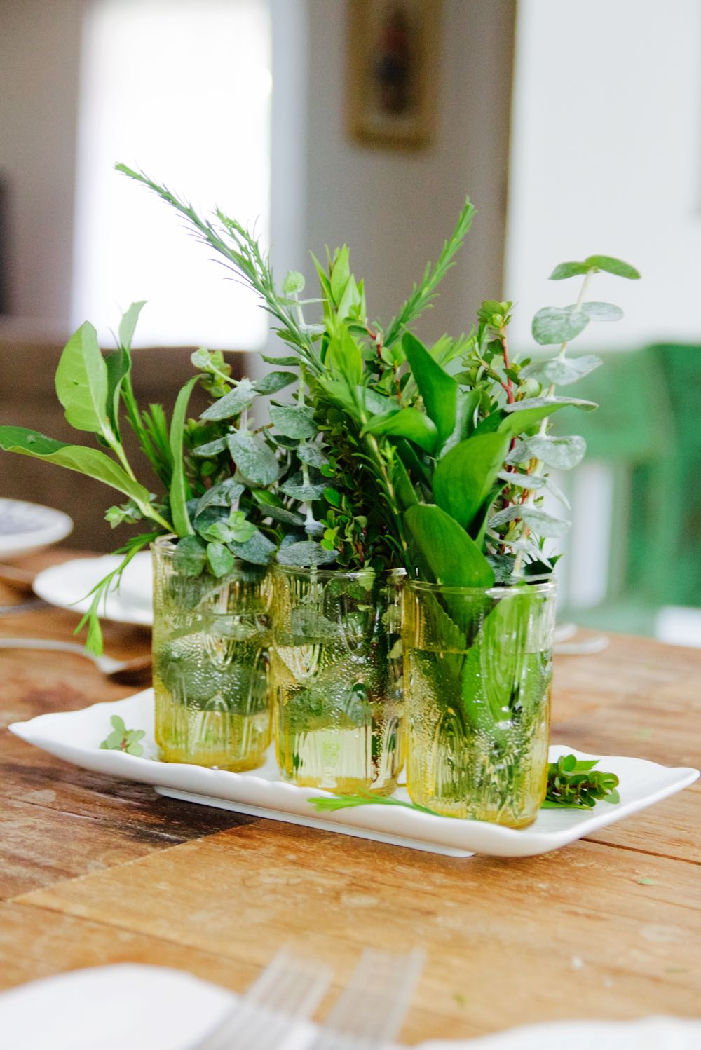 Simple centerpiece of greenery in vintage glasses