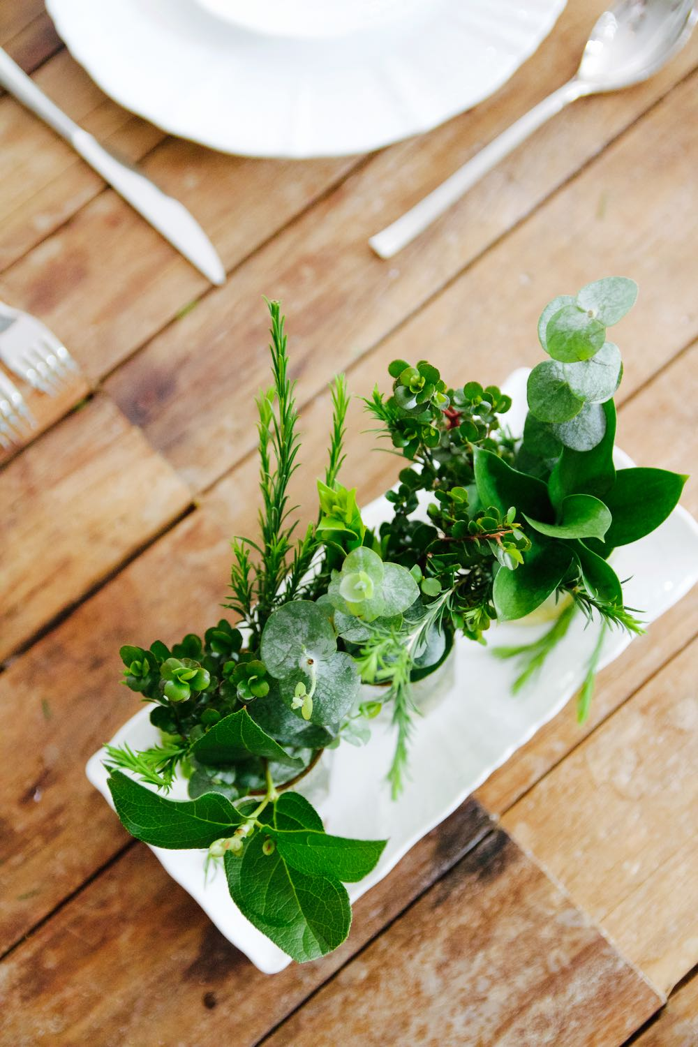 Simple centerpiece of grocery store greens in vintage glasses