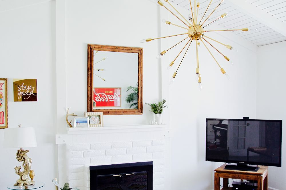 White, bright painted living room with gold chandelier