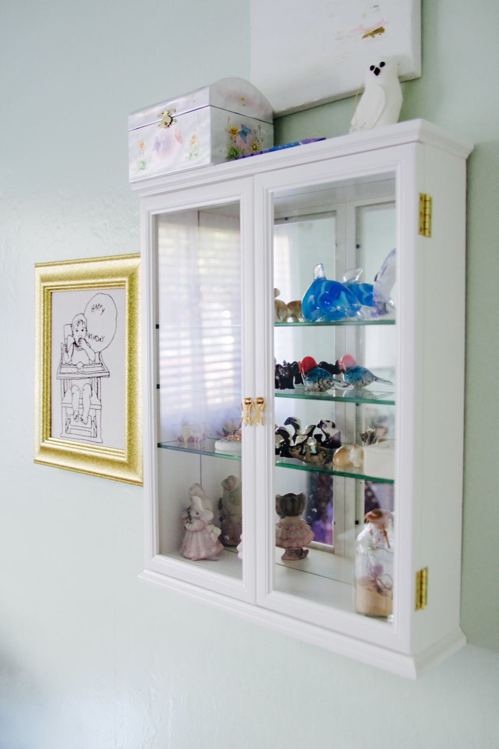 China cabinet with miniature crystal figurines