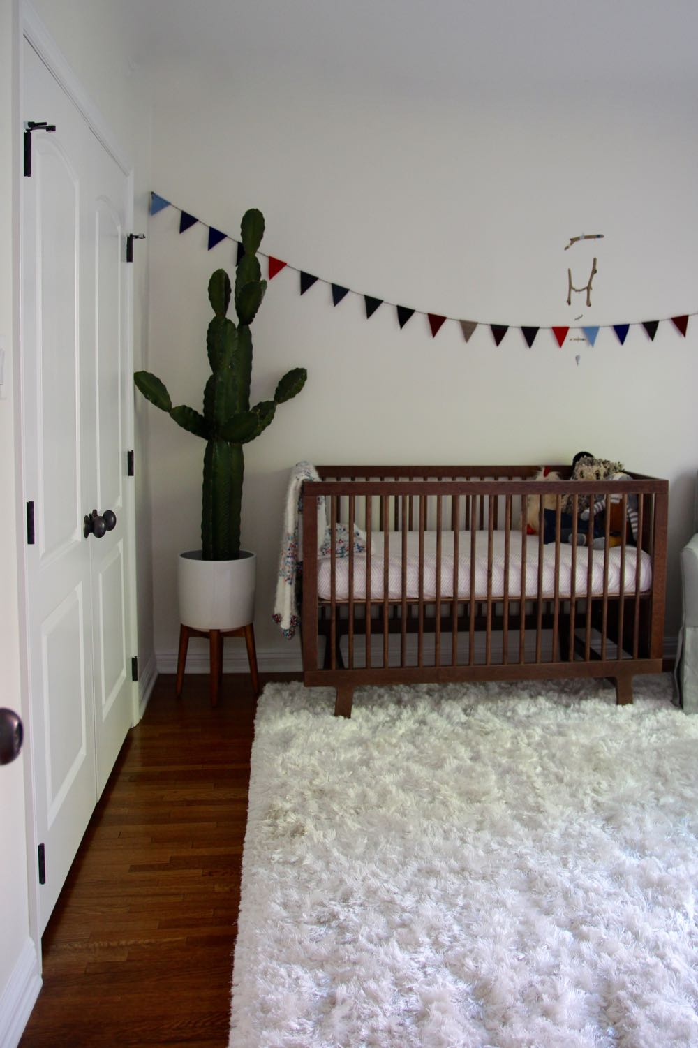 Clean and modern baby nursery with cactus and flags