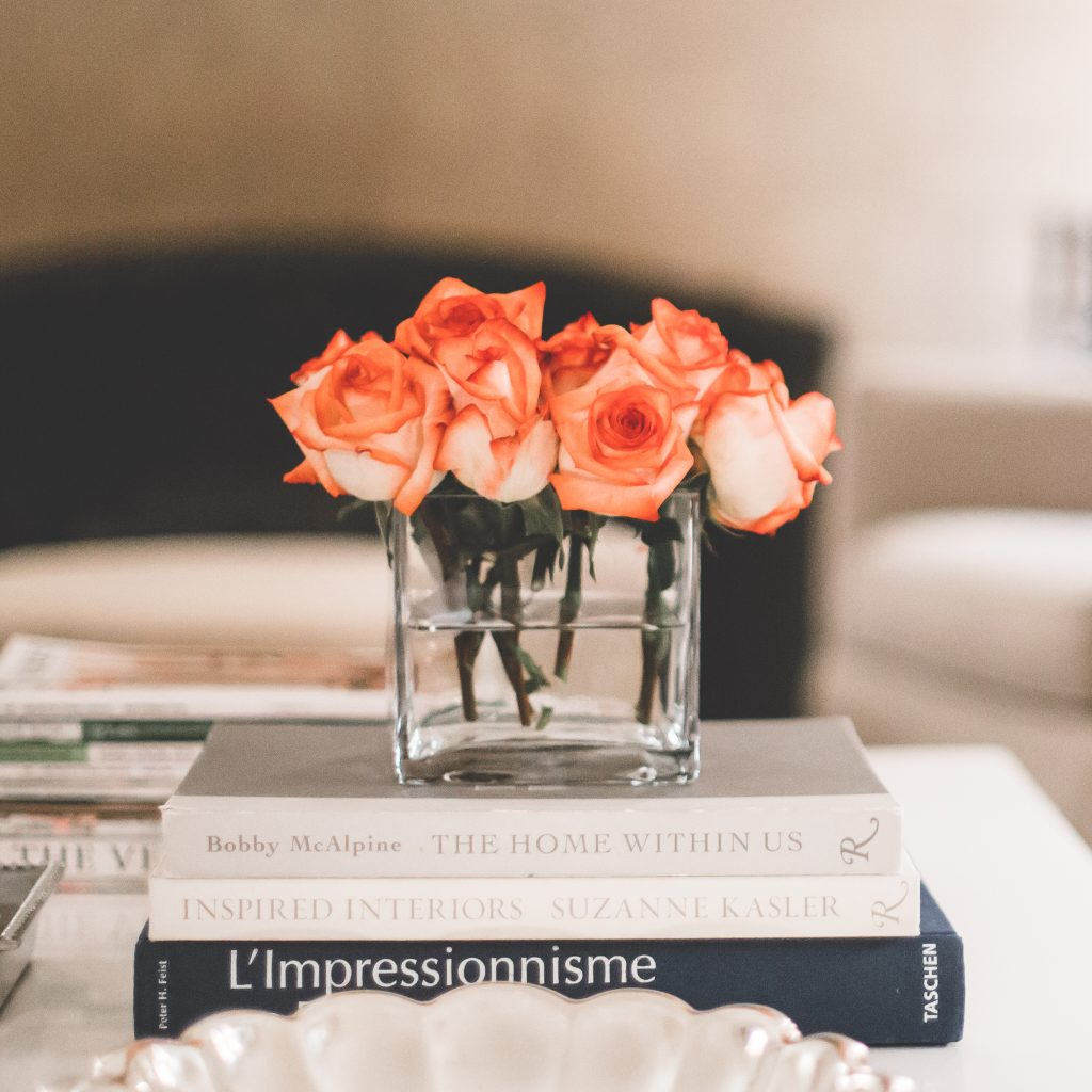 tight bunch of orange roses on a coffee table