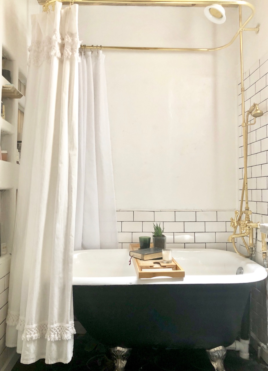 bathroom renovation with black clawfoot tub and gold fixtures